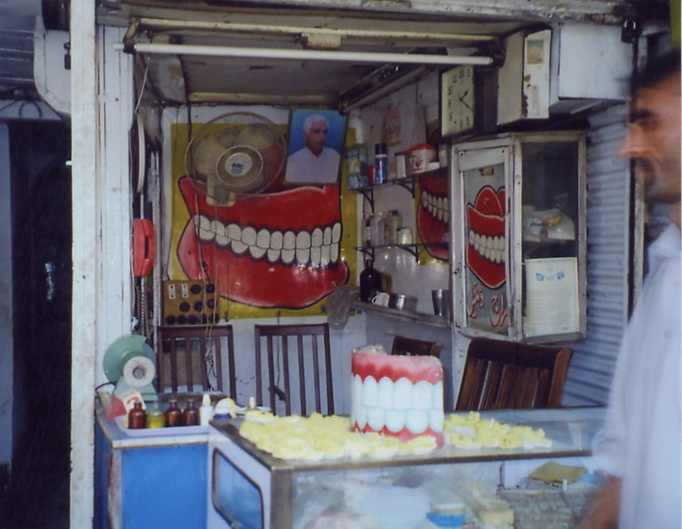 Another dentist, what you see is what you get, this is reception, examination room & store. The dentist usually sits in one of the kitchen chairs until he vacates to let the patient sit. The indistinct yellow things in the foreground are molds of people's mouths.