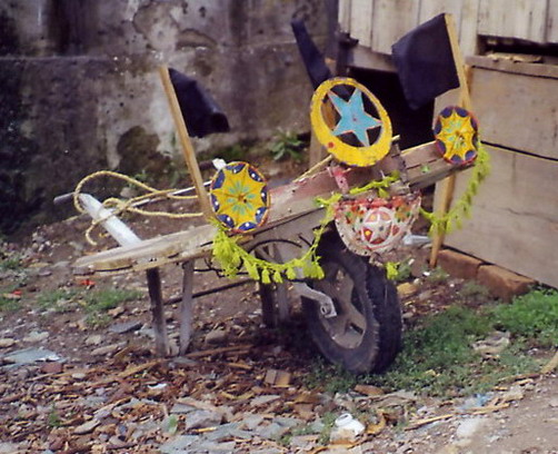 A wheel-barrow somebody went to some trouble to decorate with home-made ornaments.