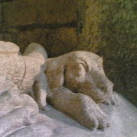 Dog at his master's feet on a stone sarcophagus